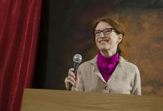 Woman at podium with microphone Stock Photo