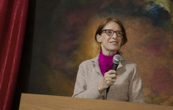 Woman at podium with microphone_1 Stock Photography