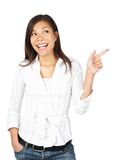 Woman pointing. And looking to the side. Casual beautiful young mixed asian / caucasian woman happy and smiling. Isolated on white background Royalty Free Stock Photo