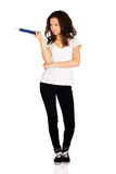 Woman pointing aside with big pencil. Royalty Free Stock Photography