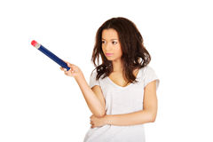 Woman pointing aside with big pencil. Stock Images
