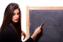 Woman pointing at a blank blackboard with a pen. Young woman pointing at a blank blackboard with a pen. On white background Royalty Free Stock Images
