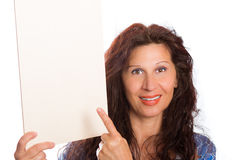 Woman pointing at blank board. Happy mature woman with Arab and Middle Eastern somatic traits and dyed with henna hair smiles pointing her finger at blank white Stock Photos