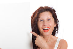 Woman pointing at blank board. Happy mature woman with Arab and Middle Eastern somatic traits and long brown hair dyed with henna smiles pointing her finger at Royalty Free Stock Photos