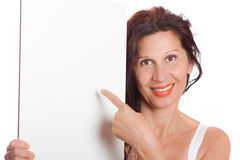 Woman pointing at blank board. Happy mature woman with Arab and Middle Eastern somatic traits and long brown hair dyed with henna smiles pointing her finger at Royalty Free Stock Image