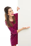 Woman pointing at blank sign. Beautiful young woman over white background Royalty Free Stock Image