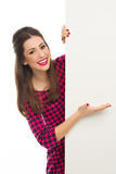 Woman pointing at blank sign. Beautiful young woman over white background Stock Image