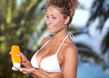 Woman pointing bottle of sun block creme in camera Stock Image