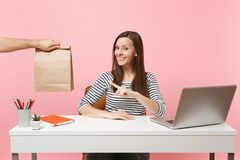 Woman pointing on brown clear empty blank craft paper bag, work at office with laptop isolated on pink background. Food. Products delivery courier service from royalty free stock photography