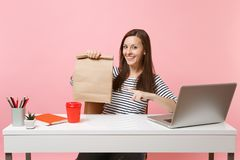 Woman pointing on brown clear empty blank craft paper bag, work at office with laptop isolated on pink background. Food. Products delivery courier service from stock photos