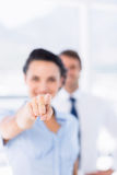 Woman pointing at camera with colleague in background Stock Images