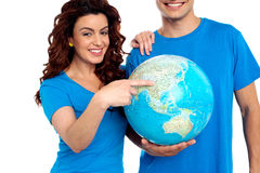 Woman pointing at China on globe. While men holds it. Cropped image, men smiling Stock Image
