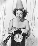 Woman pointing at the clock at midnight Stock Images