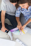 Woman pointing at color charts sitting in her new house Stock Image