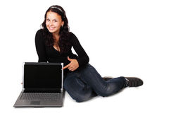 Woman pointing at computer. Young woman pointing at laptop isolated on white background Stock Photos