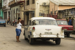 Woman pointing direction to vintage Chevy taxi Havana Stock Image