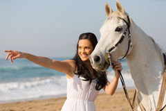 Woman pointing distance horse. Happy woman pointing at distance with her horse on the beach Royalty Free Stock Photos