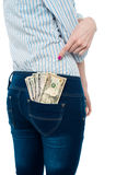 Woman pointing at dollar notes in her back pocket Stock Photos