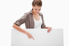 Woman pointing down at blank signboard Royalty Free Stock Photography