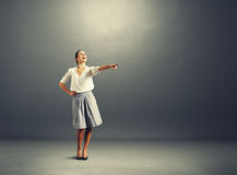 Woman pointing at empty copyspace in dark room Royalty Free Stock Photo