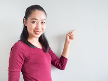 Woman pointing on empty wall. Stock Photography
