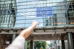 Woman pointing on the european flag. Woman pointing with hand on the european flag on the parliament building in Brussel Stock Images