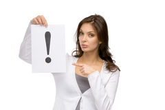 Woman pointing at exclamatory mark. Half-length portrait of woman pointing at the exclamatory mark she hands, isolated on white. Concept of problem and solution Stock Images