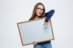 Woman pointing finger on blank board. Portrait of a cute beautiful woman pointing finger on blank board isolated on a white background Royalty Free Stock Photography
