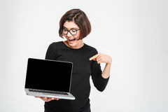 Woman pointing finger on blank laptop computer screen Royalty Free Stock Images