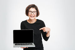 Woman pointing finger on blank laptop computer screen. Laughing woman pointing finger on blank laptop computer screen isolated on a white background Stock Photos