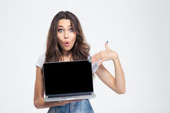 Woman pointing finger on blank laptop computer screen. Portrait of a happy woman pointing finger on blank laptop computer screen isolated on a white background Stock Image