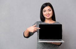 Woman pointing finger on blank laptop computer screen. Portrait of a smiling woman pointing finger on blank laptop computer screen over gray background Stock Photo