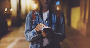 Woman pointing finger on blank screen smartphone on background bokeh light in night atmospheric city, blogger hipster using in han. Ds gadget mobile phone stock photo