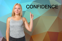 Woman pointing finger 'Confidence' inscription. Smiling young woman pointing finger 'Confidence' inscription Royalty Free Stock Images