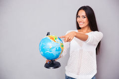 Woman pointing finger at globe Royalty Free Stock Images