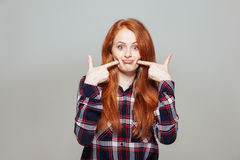 Woman pointing finger at her cheek Royalty Free Stock Image