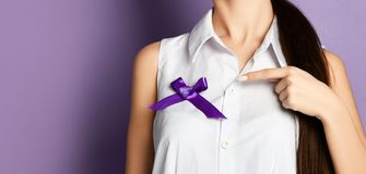 Woman pointing finger on purple ribbon to world epilepsy day. Alzheimer`s disease, pancreatic cancer. Epilepsy and fibromyalgia awareness stock images
