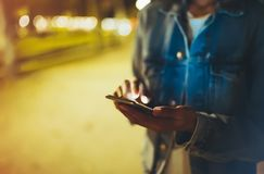 Woman pointing finger on screen smartphone on background illumination bokeh light in night atmospheric city, hipster using in hand. S mobile phone closeup royalty free stock images