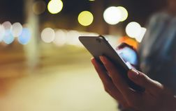Woman pointing finger on screen smartphone on background illumination bokeh light in night atmospheric city, hipster using in hand. S mobile phone closeup stock photography