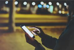 Woman pointing finger on screen smartphone on background illumination bokeh light in night atmospheric city, hipster using in hand stock photo