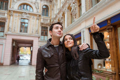 Woman pointing finger on something to her boyfriend. Portrait of a smiling women pointing finger on something to her boyfriend outdoors in old european city Royalty Free Stock Photography