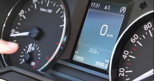 Woman pointing finger to car odometer with 19999 km miles. Woman pointing finger to modern car odometer with speedometer showing 19999 km on the board of a new stock footage