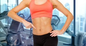 Woman pointing finger to her abdomen in gym Royalty Free Stock Photos