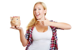 Woman pointing with finger to piggy bank Stock Photo