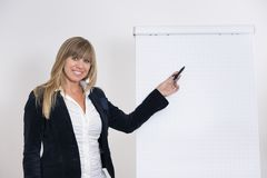 Woman is pointing at a flip chart Stock Images
