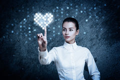 Woman Pointing at Glowing Digital Heart Stock Image