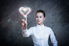 Woman Pointing at Glowing Heart Stock Images