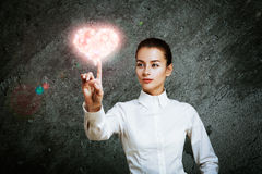 Woman Pointing at Glowing Pink Heart Stock Images
