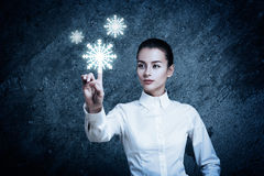 Woman Pointing at Glowing Snow Icon. Beautiful Woman Pointing at Glowing Snow Icon. Perfect Winter Season Concept. Futuristic Weather Forecast Visualization Royalty Free Stock Images