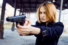Woman pointing a gun. Mafia girl shooting at someone on the street. Royalty Free Stock Photo